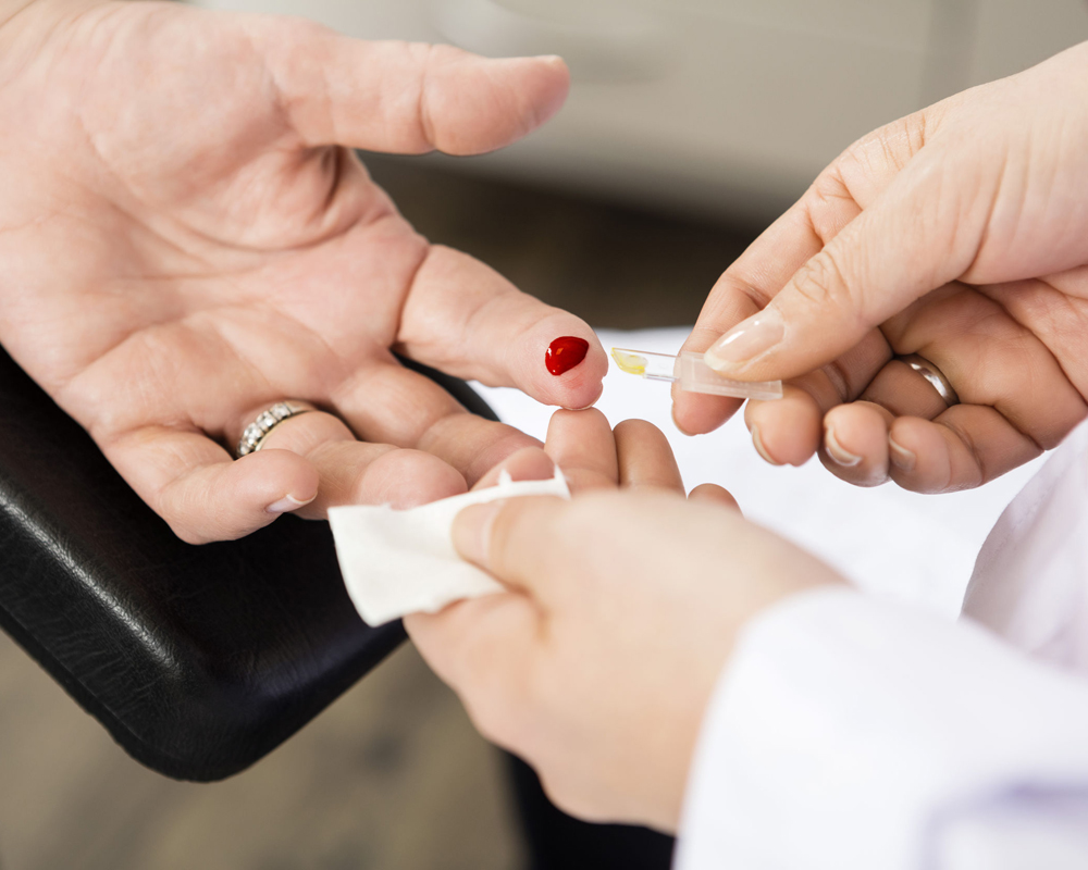 Image of someone's finger being pricked for bloodwork sample.