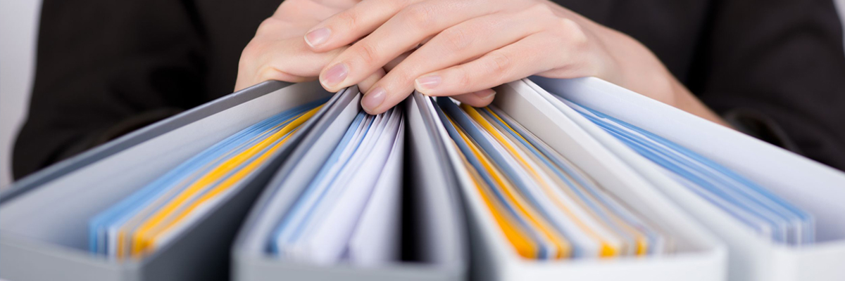 Close up image of hands resting on a group of binders.