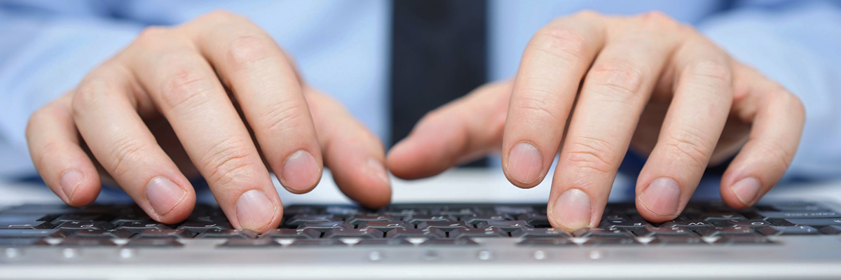 Image of business man's hand typing on a keyboard.